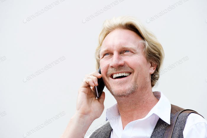 middle aged man talking on mobile phone against white wall