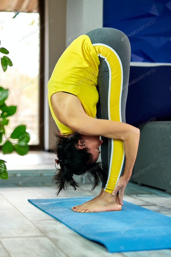 Senior woman stretching her body, yoga at home.