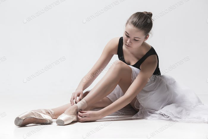 Ballerina dancer sitting down with her legs crossed