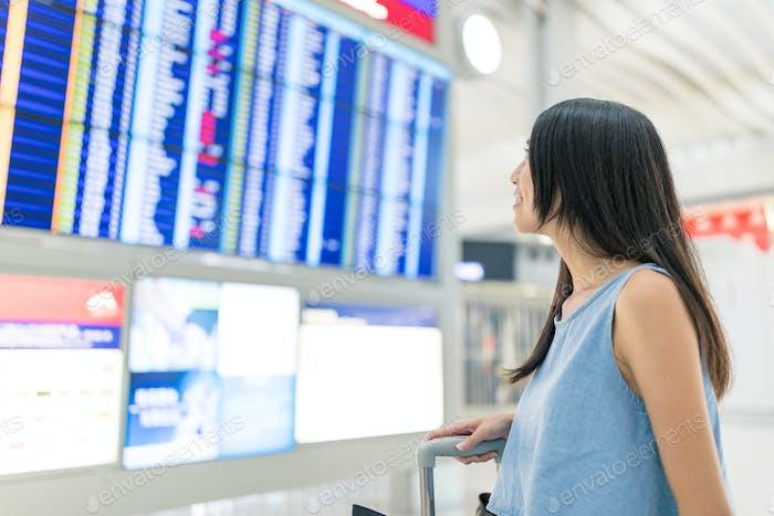 Mujer de viaje mirando el monitor de número de vuelo