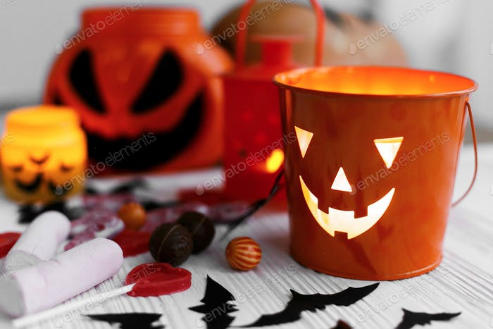 Halloween candy , jack o lantern bucket, candle and skulls