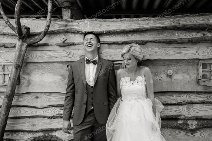 beautiful young wedding couple stands near house
