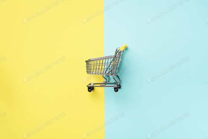 Shopping cart on blue and yellow background. Minimalism style. Creative design. Top view with copy
