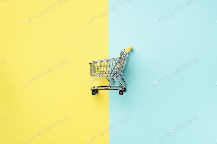 Warenkorb auf blauem und gelbem Hintergrund. Minimalismus Stil. Kreatives Design. Draufsicht mit Kopie