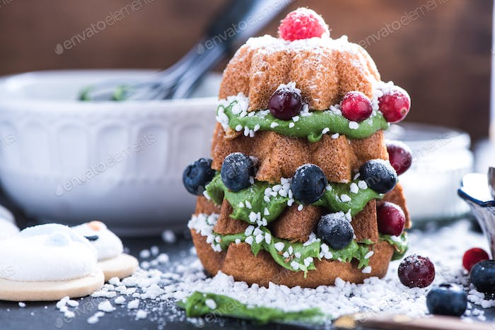 Decorating Christmas tree cake with fruits