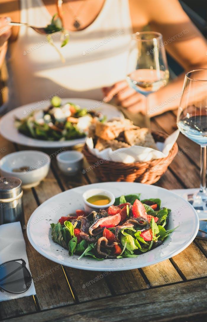 Junge Frau essen Salat und trinken Wein im italienischen Café