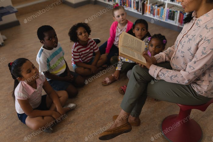 Female teacher reading a story to her schoolkids in school library