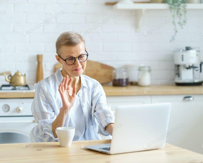 Modern happy senior woman wearing eyeglasses waving at webcamera on laptop while studying online