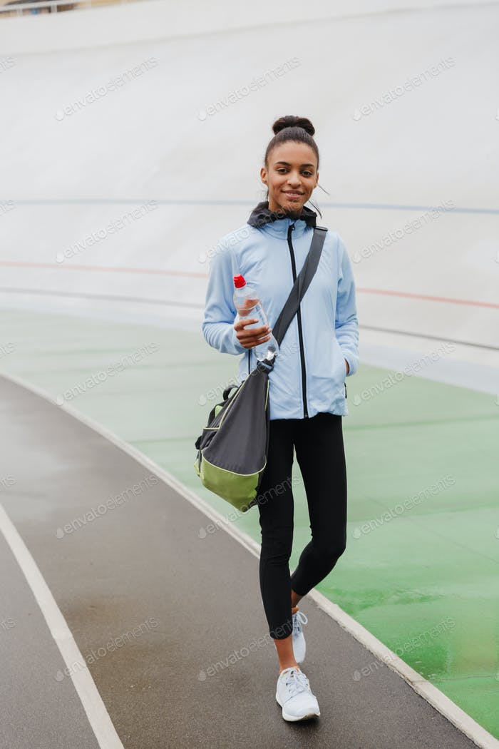 Smiling fit young african sportswoman carrying sportsbag