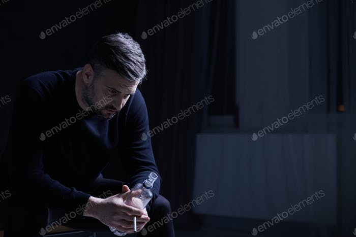 Man sitting and holding a bottle