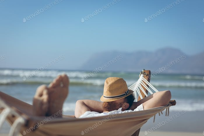 Front view of young Caucasian man relaxing on hammock at beach on a sunny day