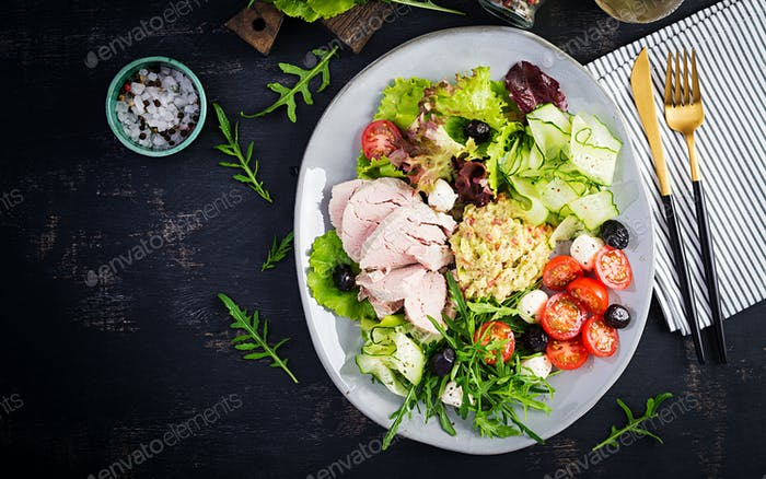 Dinner dish with boiled pork meat, avocado guacamole, tomatoes, cucumbers, mozzarella cheese,