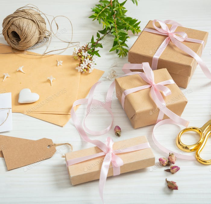 Flat lay of gift boxes and invitations on a white wooden tabletop.