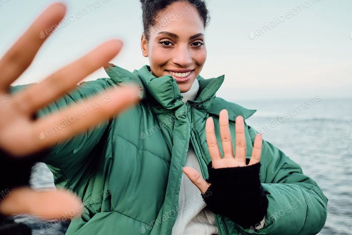 Pretty joyful African American girl in down jacket happily pulling hands to camera by the sea