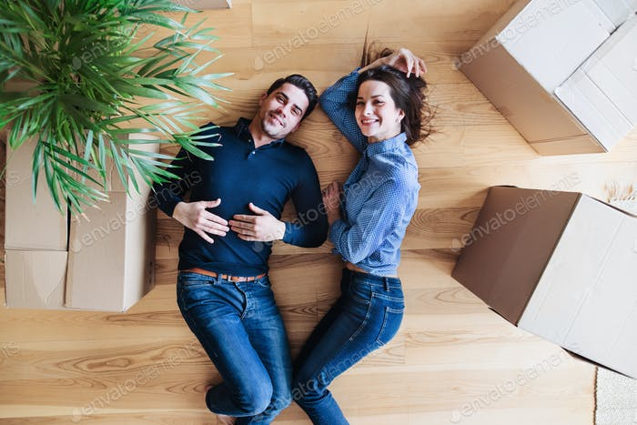A top view of young couple moving in a new home, lying down on the floor.