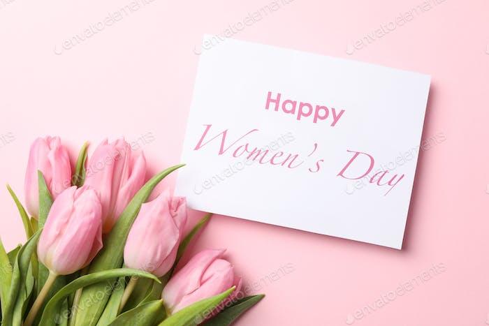 Rosa Tulpen und Inschrift Glücklicher Frauentag auf rosa Hintergrund, Draufsicht