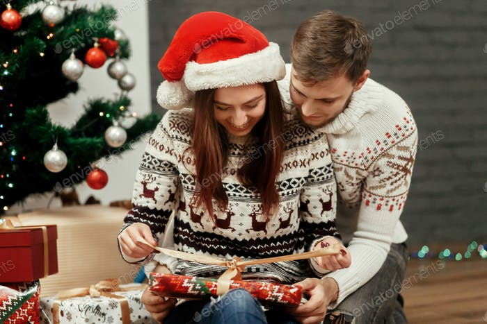 Happy boyfriend and girlfriend couple near christmas tree