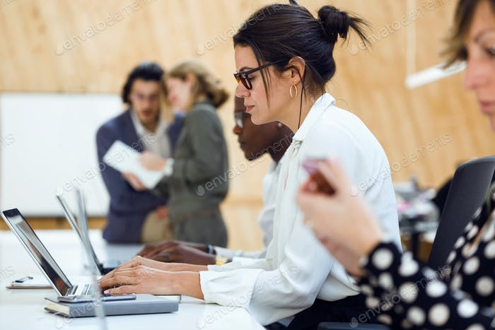Pretty elegant businesswoman working with laptop in coworking pl