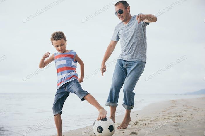Vater und Sohn spielen Fußball am Strand zur Tageszeit.
