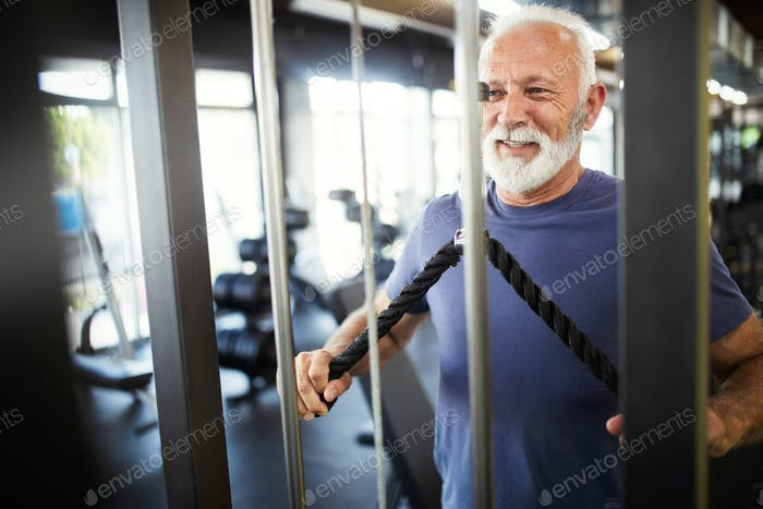 Happy fit mature man in gym working out to stay healthy