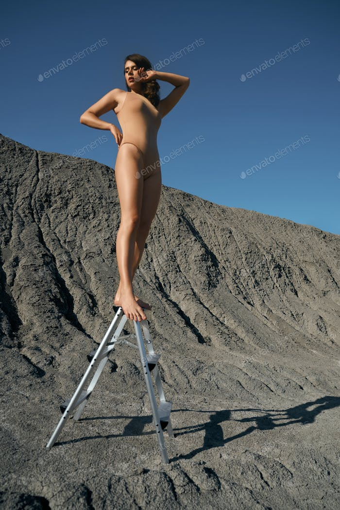 Woman wearing swimsuit posing on ladder in quarry