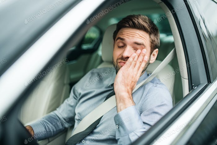 Young bored business man with shirt and tie sitting in car