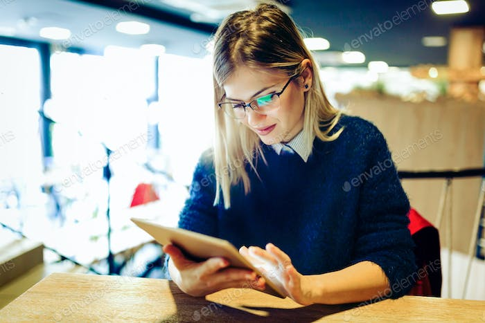 Happy young woman drinking coffee and using tablet