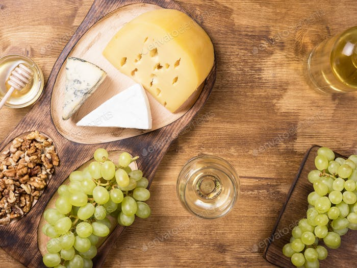 Flat lay top view of various cheeses next to fresh grapes, glass of wine on a wooden table