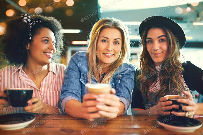Three trendy young women enjoying coffee