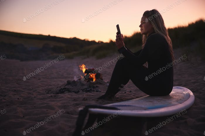 Woman Sitting On Surfboard By Camp Fire On Beach Using Mobile Phone As Sun Sets Behind Her