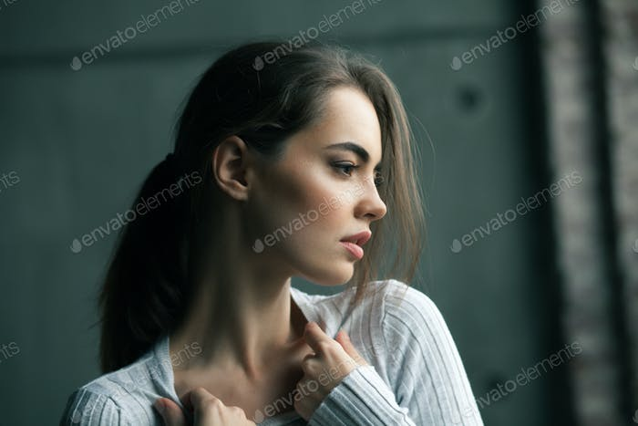 Young passionate woman in white shirt near the grey wall