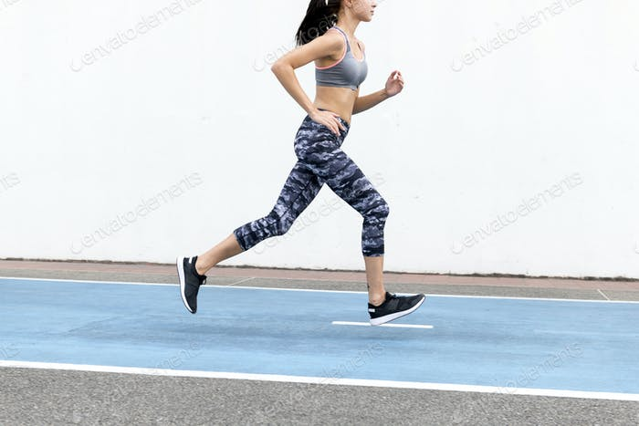 White woman running on track