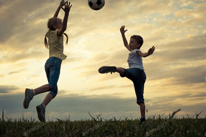 Happy young little boy and girl playing in the field  with socce