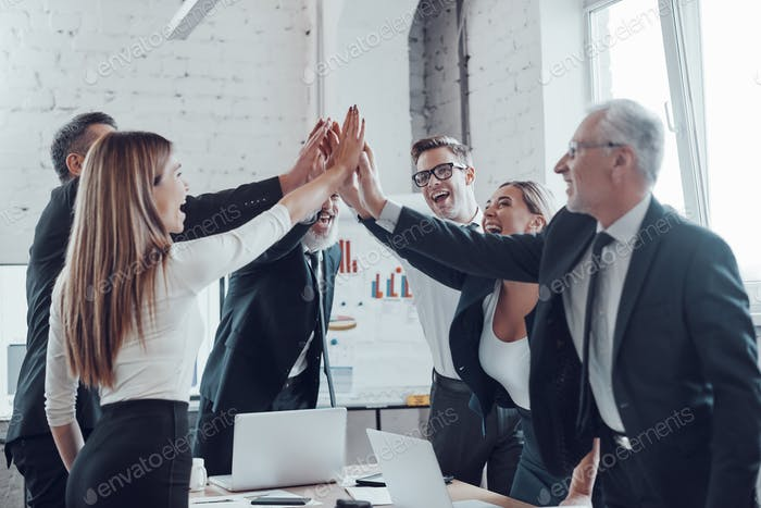 Cheerful business team giving each other high five to success while working in the modern office