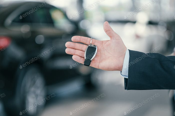 Giving a key from new car at dealership showroom