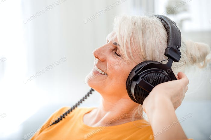 Relaxed senior woman listening her favourite music at home using big headphones