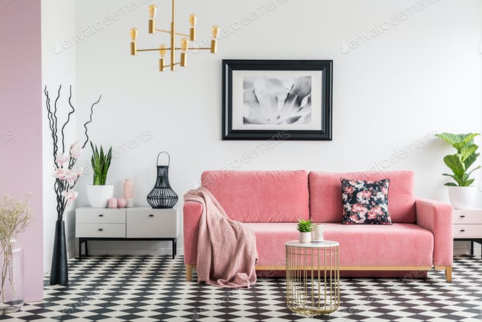 Pink blanket on settee in white living room interior with plants