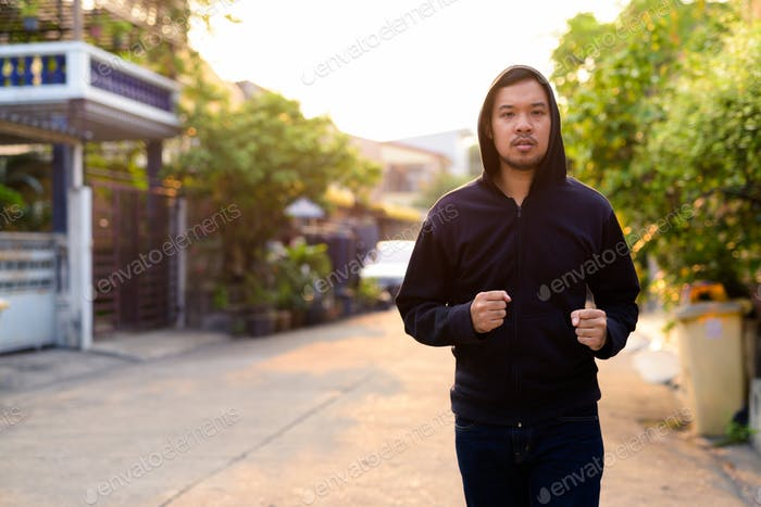 Young Asian man with hoodie jogging in the streets outdoors