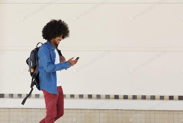 Estudiante masculino caminando con bolsa y teléfono Móvil
