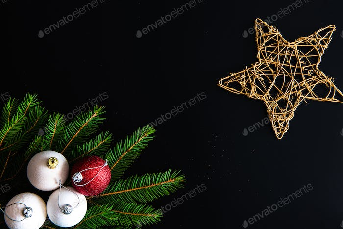 Christmas background with balls, golden snowflake, fir tree branches on black