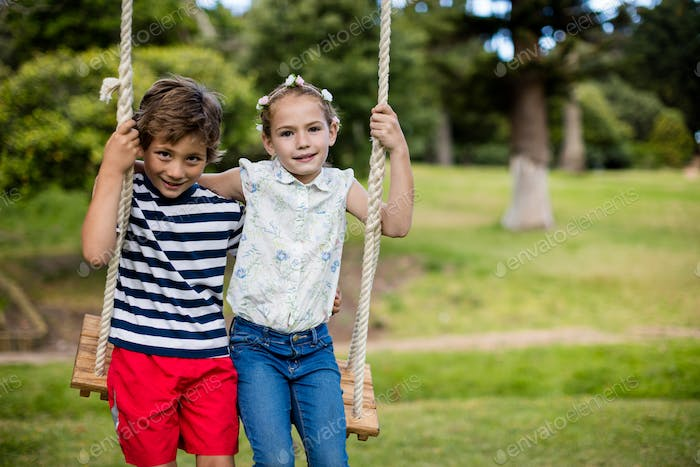 Boy and girl sitting on a swing in park