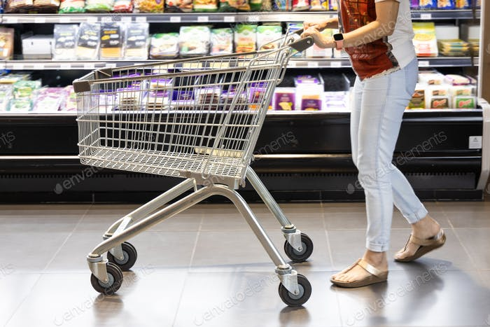 Woman with trolley shopping cart browsing merchandise in modern supermarket