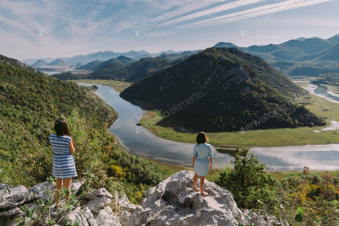 women travel and relax in mountains looking at panorama view