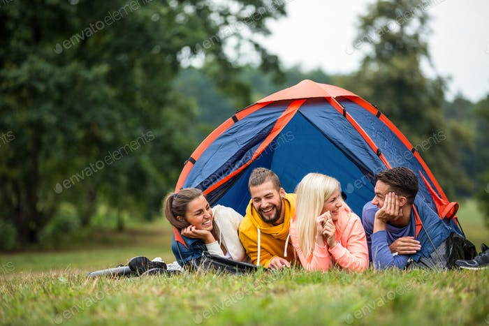 Happy friends lying in their tent in the countryside