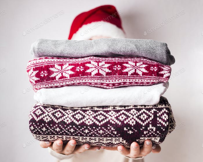 Woman holding winter sweaters with patterns on background