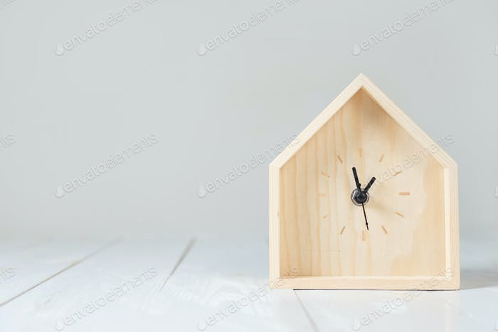 Wooden table clock in the shape of a house.