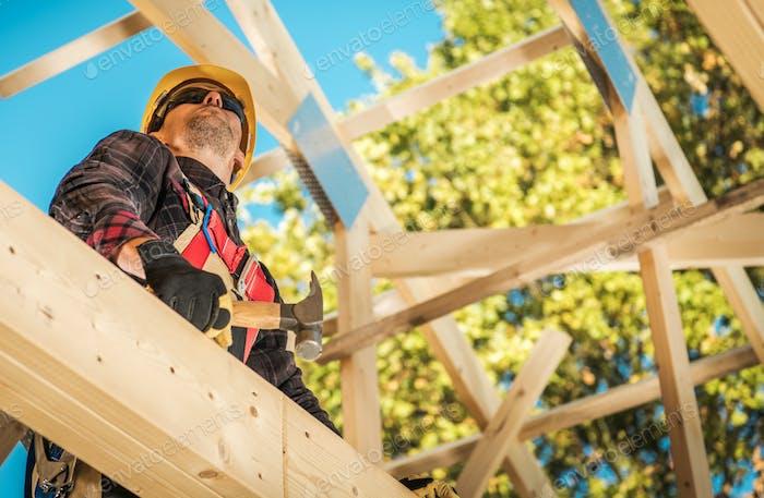 Construction Worker Between Wooden House Skeleton