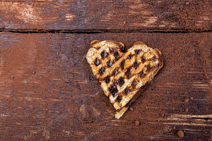 One belgian heart shaped waffle with chocolate on wooden background. Flat lay. Copy space