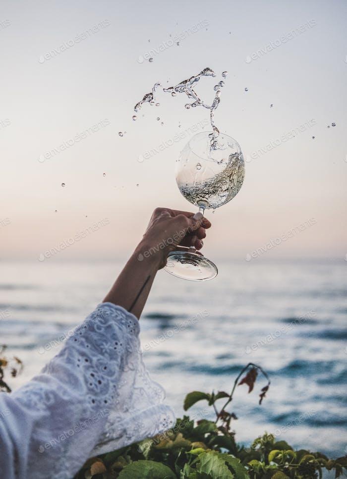Frau fließenden Weißwein aus Weingass über schönen Sonnenuntergang