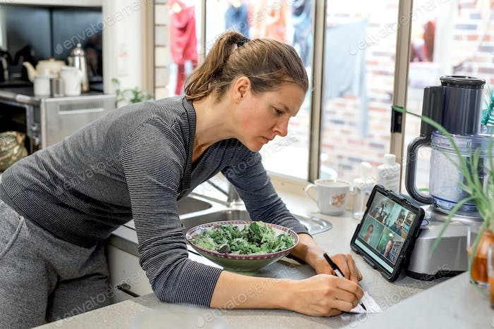Woman in the kitchen watching zoom-meeting on tablet and writes notes